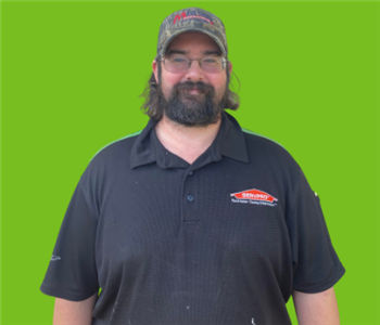 Male SERVPRO employee on green background