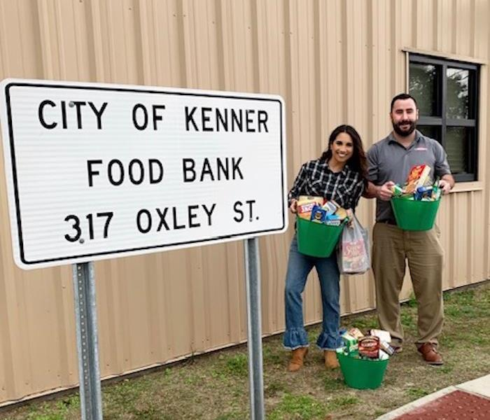 Marketing Reps Shelby Clement and Jake Olivier Dropping off  food in front of Kenner Food Bank