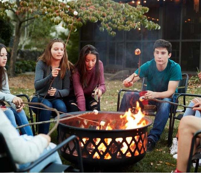 Group of teens around fire pit roasting marshmallows