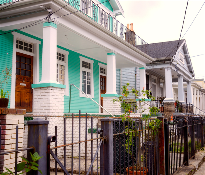 Typical Teal New Orleans Home With Gate in Front